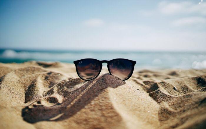 Sonnenbrille am Strand vor blauem Himmel